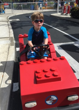 The Boy driving a firetruck on a track for 3 to 4 year olds only